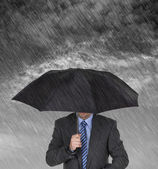Businessman sheltering — Stock Photo