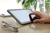 Finger touching screen of a digital tablet — Stock Photo