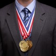 Succesful businessman with gold medals — Stock Photo #24557325