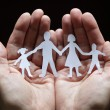 Paper chain family protected in cupped hands — Stock Photo #24559953