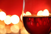 Glass of red wine against defocussed lights — Stock Photo