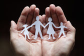 Paper chain family protected in cupped hands — Stok fotoğraf