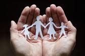 Papírový řetěz rodina chráněna v dlaní — Stock fotografie