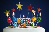 Happy birthday candles on a cake — Stock Photo