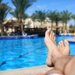 Mans legs by swimming pool — Stock Photo #44080493