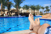 Mans legs by swimming pool — Stock Photo