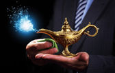 Businessman holding magic Aladdins genie lamp — Stock Photo