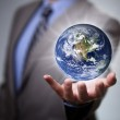 Businessman holding the world in his hands — Stock Photo #49283469