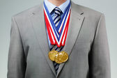 Succesful businessman with gold medals — Stock Photo