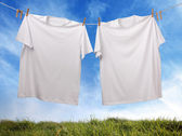 Blank white t-shirt hanging on clothesline — Stok fotoğraf