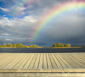 Empty wooden jetty and rainbow — Stock Photo