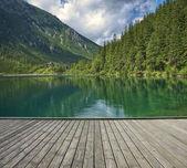 Pier with mountain lake — Stock Photo