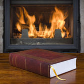 Old book and fireplace — Stock Photo