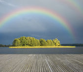 Wooden jetty and rainbow — Stock Photo