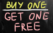 """Buy one"" handwritten with white chalk on a blackboard — Stock fotografie"