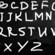 English alphabet handwritten with white chalk on a blackboard — Stock Photo