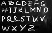 English alphabet handwritten with white chalk on a blackboard — Stock Photo