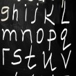 Complete english alphabet handwritten with white chalk on a blac — Stock Photo #28201635