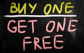 """Buy one"" handwritten with white chalk on a blackboard — Stock Photo"
