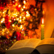 Holy Bible with candle on bokeh — Photo