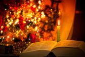Holy Bible with candle on bokeh — Stock Photo