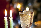 Glasses of champagne with candle on bokeh — Stock Photo