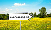 Job vacancies on a sign before a meadow — Stock Photo
