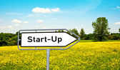 "Sign ""Start-Up"" before a meadow — Stock Photo"