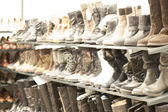 Shoes and boots in a rack — Stock Photo