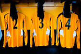 Football teams dressing room with numbered shirts — Stock Photo