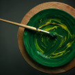 Artists paint brush and paint green on white canvas. — Stock Photo