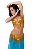 Beautiful belly dancer wearing a gold and blue costume. — Stock Photo