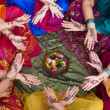 Six pairs of henna decorated female hands arranged in a circle on a colorful background. - Stock Photo