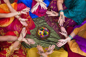 Six pairs of henna decorated female hands arranged in a circle on a colorful background. — Stock Photo