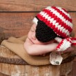 Royalty-Free Stock Photo: One week old newborn baby boy wearing a crocheted red and white pirate hat and black eye patch.