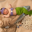 Newborn baby girl wearing a crocheted green and lavender colored mermaid costume. — Stock Photo