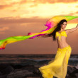 A beautiful bellydancer poses with a flowing yellow silk veil and standing on a rocky bank in front of the Atlantic Ocean — Stock Photo #25592781