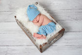 Newborn baby wearing blue and white striped pajamas and sleeping in a vintage, wooden, soda pop crate. — Стоковое фото
