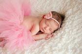 Nyfödd baby flicka klädd i en rosa virkade pannband och tutu. — Stockfoto