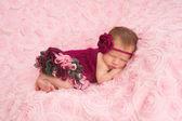 A sleeping newborn baby girl wearing a maroon crocheted headband and romper. — Stock Photo