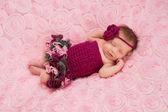Sleeping newborn baby girl wearing a maroon crocheted headband and romper — Stock Photo