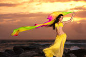 A beautiful bellydancer poses with a flowing yellow silk veil and standing on a rocky bank in front of the Atlantic Ocean — Stock Photo