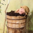 7 day old newborn baby boy sleeping in an old, weathered wooden bucket. — Stock Photo #25677073