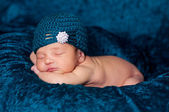 Newborn girl sleeping on a teal blanket and wearing a teal crocheted flapper-style hat with rhinestone embellishment. — Stock Photo