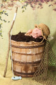 7 day old newborn baby boy sleeping in an old, weathered wooden bucket. — Stock Photo