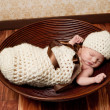 Newborn baby girl sleeping in a crocheted cream colored cocoon She is wearing a matching beanie hat and lying in a brown bowl - Stockfoto