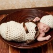 Newborn baby girl sleeping in a crocheted cream colored cocoon She is wearing a matching beanie hat and lying in a brown bowl - Stock fotografie