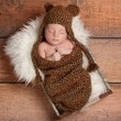 Newborn baby boy wearing a brown crocheted bear hat and sleeping in a vintage wooden box. — Stock Photo