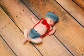 Newborn baby boy wearing a vintage inspired grey and red little man suit consisting of suspenders, bow tie and newsboy hat. — Stock Photo