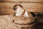 Newborn baby boy sleeping in an old wooden banded bucket. — Stock Photo